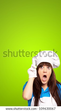 portrait of female chef shocked on green background