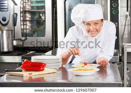 Portrait of female chef sprinkling spices on food at commercial kitchen counter