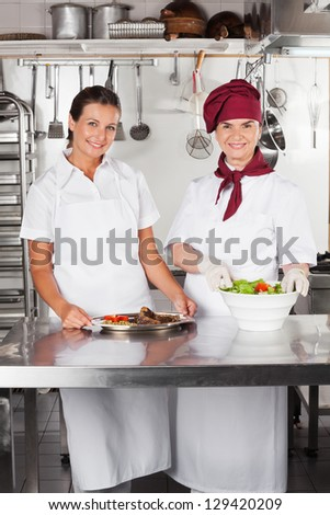 Portrait of female chefs with dishes standing at kitchen counter