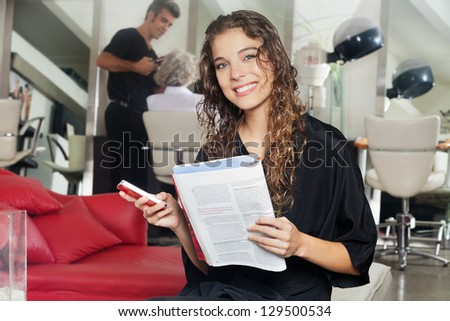 Portrait of female client holding mobile phone and magazine with hairdresser working in the background at hair salon