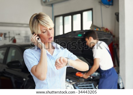 portrait of female client talking on mobile phone in auto repair shop.