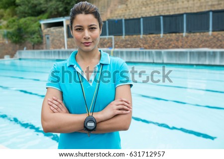 Portrait of female coach standing with arms crossed near poolside Stockfoto ©