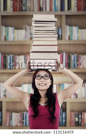 Portrait of female college student carrying a pile of books over her head. shot in library