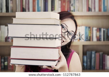 Portrait of female college student smiling behind thick books. shot in the library