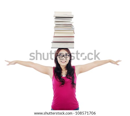 Portrait of female college student stretches her hands with a pile of books on her head