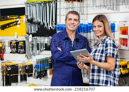 Portrait of female customer and male vendor with digital tablet in hardware store