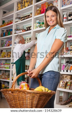 Portrait of female customer holding shopping basket with salesman in background