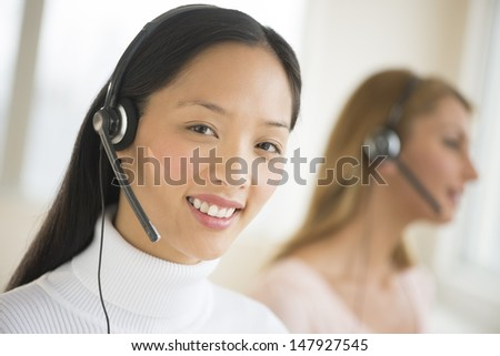 Portrait of female customer service representative smiling at office with colleague working in background