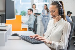 Portrait of female customer support or sales agent. Caller or receptionist phone operator working in call center.