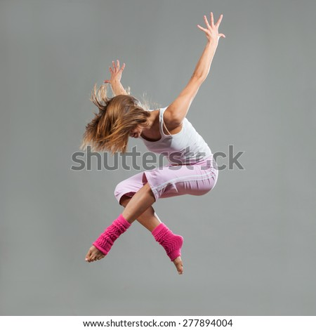 Portrait of female dancer performing in mid air. Jumping pose concept.