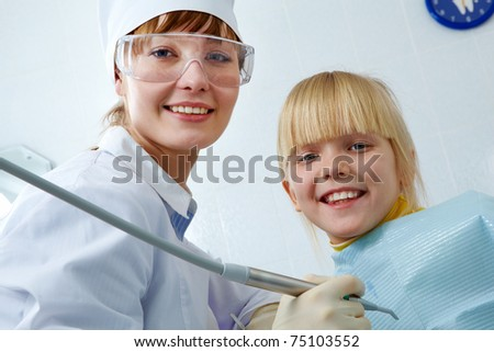 Portrait of female dentist and little girl looking at camera