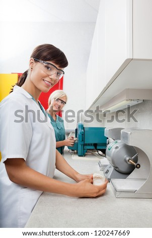 Portrait of female dentist holding dental plaster mold with assistant at clinic