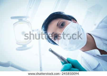 Portrait of female dentist in surgical mask holding dental drill