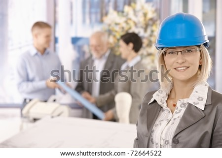 Portrait of female designer in hardhat smiling at camera, colleagues working in background.?