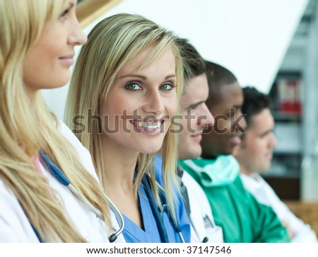 Portrait of female doctor smiling at the camera with her team in a line on stairs