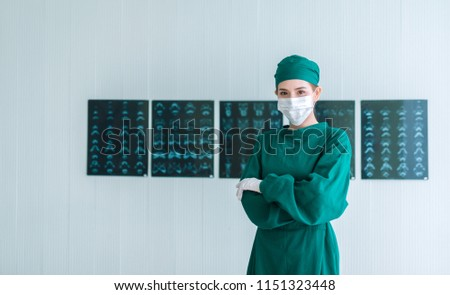 Portrait of Female doctor Surgeon in green scrubs putting on surgical gloves and looking at Camera . Young asian doctor woman with x-ray image background in hospital