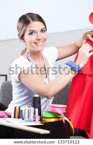 Portrait of female dressmaker adjusting clothes.
