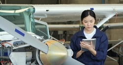Portrait of Female engineer or pilot using tablet to research information for her project. Female engineer repairing a jet engine with concentration. Transportation and Technology