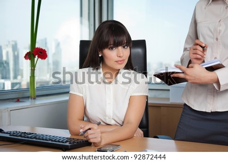 Portrait of female executive smiling with colleague standing beside her with calender