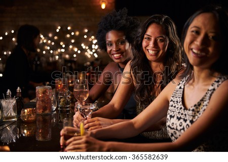 Portrait Of Female Friends On Night Out At Cocktail Bar #365582639