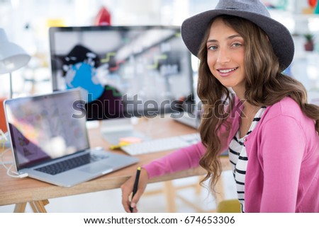Portrait of female graphic designer working at desk in the office