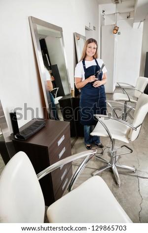 Portrait of female hairdresser holding hair straightened at salon