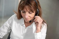 Portrait of female helpline operator in headset