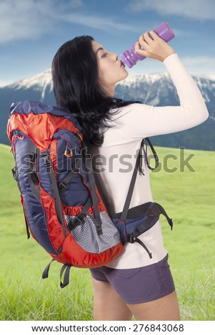 Portrait of female hiker carrying backpack and take a break while drinking fresh water from the bottle