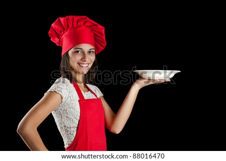 Portrait of female in chef uniform and chef hat showing plate