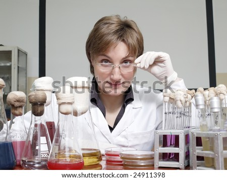 Portrait of female laboratory technician sitting behind laboratory desk with flasks and test tubes