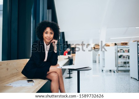 Portrait of female lawyer in trendy formal wear working on modern computer looking at camera, confident businesswoman spending time for research information on banking website using 4G internet