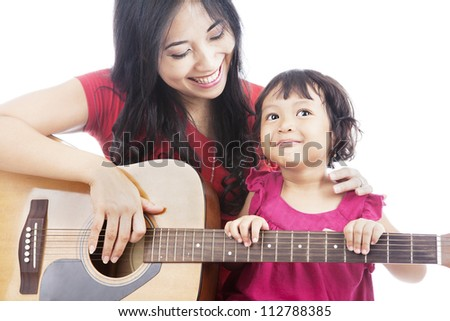 Portrait of female musician plays guitar with her daughter