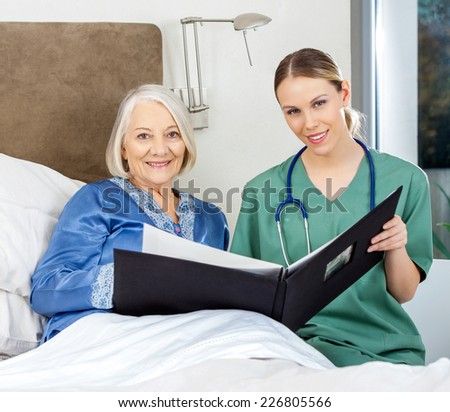 Portrait of female nurse and senior woman with medical reports in bedroom at nursing home