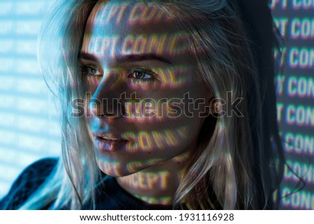 Portrait of female on blue neon light digital interface background. Beautiful young woman. Concept. Digital art. Projector light illumination on face. Stock photo ©