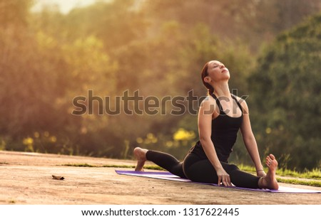 Portrait of female practicing yoga by 180 degree split leg posture with nature during sunrise in the morning. Peaceful, mindfulness and Healthcare concept.