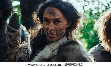 Portrait of Female Primeval Cavemen Leader and Warrior Threat Enemy with Stone Tipped Spear, Scream, Defending Their Cave and Territory in the Prehistoric Times. Neanderthals / Homo Sapiens Tribe