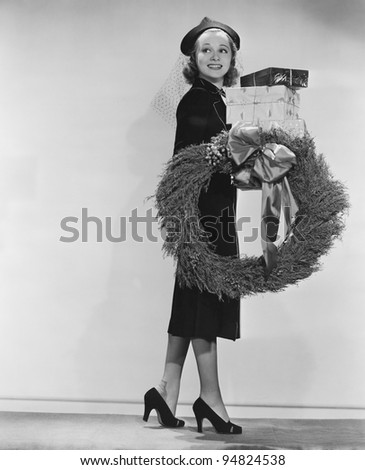 Portrait of female shopper with wreath and Christmas gifts