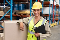 Portrait of female staff smiling while standing in warehouse. This is a freight transportation and distribution warehouse. Industrial and industrial workers concept