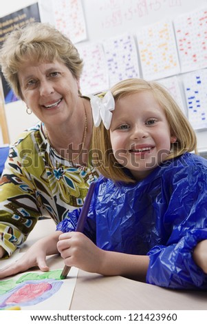 Portrait of female student painting with teacher in art class
