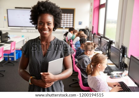 Photo of Portrait Of Female Teacher Holding Digital Tablet Teaching Line Of High School Students Sitting By Screens In Computer Class