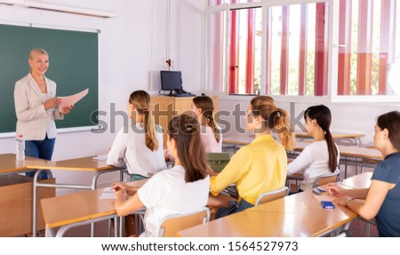 Portrait of female teacher lecturing to students at auditorium #1564527973