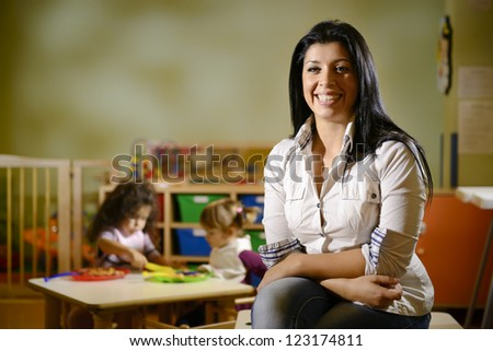 Portrait of female teacher smiling at camera and happy children eating lunch at school. Copy space