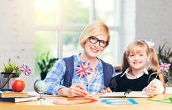 Portrait of female teacher studying with kid girl in light white classroom, children learning concept