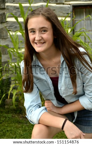 Portrait of female teen smiling and leaning on one knee with rustic log cabin background #151154876