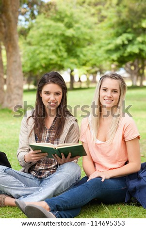 Portrait of female teenagers sitting with a textbook in a park
