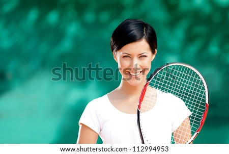 Portrait of female tennis player with racket at the tennis court. Outdoors
