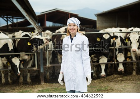 Portrait of female vet working with cows in farm outdoors