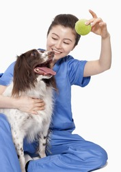 Portrait of female veterinarian holding a ball with a dog