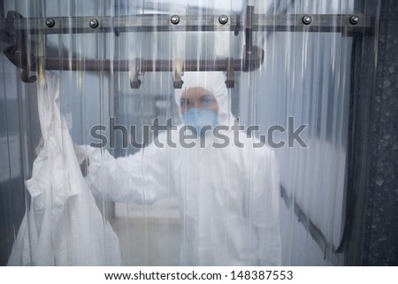 Portrait of female worker in protective mask and suit behind plastic wall at lab