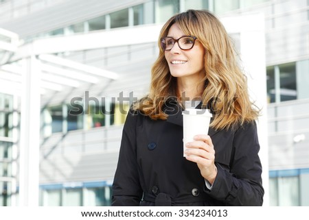 Portrait of financial professional woman holding in hand a cup of coffee while standing in front of office building after meeting.